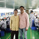 Dr. Wu inside cell phone factory with it's HR manager.